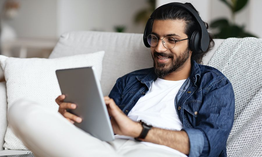 Handsome Arab Guy In Wireless Headphones Using Digital Tablet At Home, Browsing Internet Or Shopping